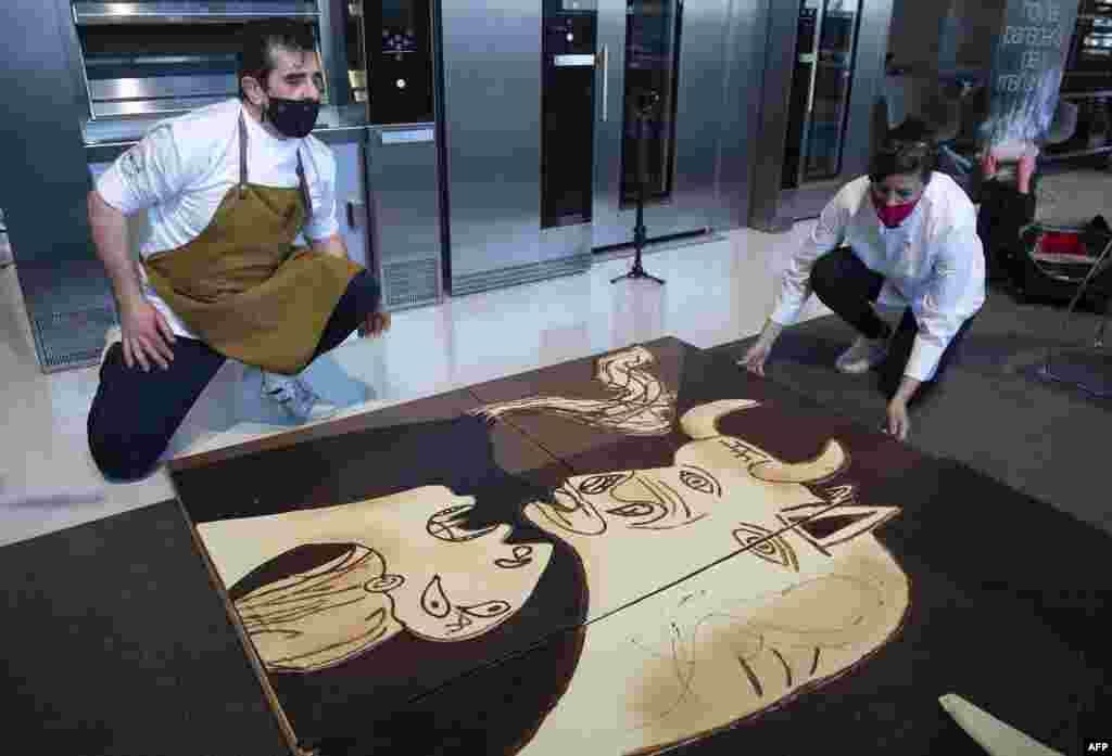 """Members of Euskal Gozogileak (Basque Confectioners) association work on a life-size chocolate version of Picasso's painting """"Guernica"""" in the Spanish Basque town of Lezo."""