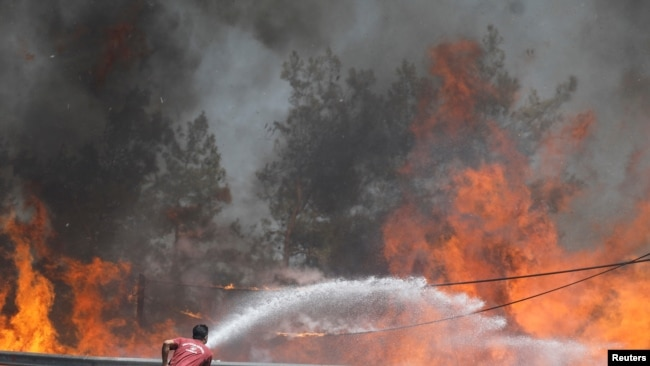 Seorang pemadam kebakaran mencoba memadamkan api kebakaran lahan dekat Marmaris, Turki, 1 Agustus 2021.