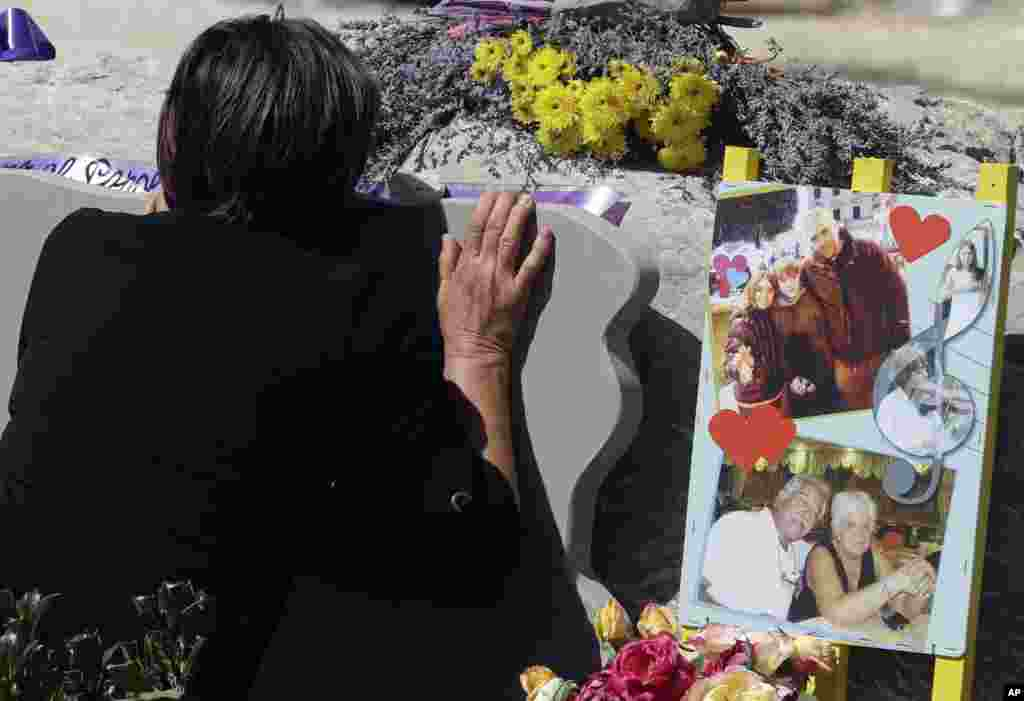 A woman mourns in front of a memorial site for the victims of the earthquake, in Amatrice, central Italy, a year after a deadly quake hit the area leaving nearly 300 people dead.