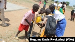 South Sudan children use a jerry can filled with water to wash their hands in Juba.