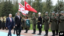 Turkish Prime Minister Binali Yildirim, left, and Tufan Erhurman, the prime minister of the self-declared Turkish Cypriot state in the north of the divided island, review a military honour guard during a ceremony at the Cankaya Palace in Ankara, Turkey, Wednesday, March 7, 2018.