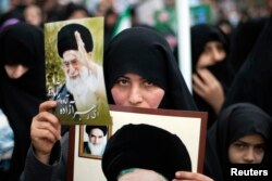 FILE - A woman holds pictures of Iran's Supreme Leader Ayatollah Ali Khamenei (top) and late Leader Ayatollah Ruhollah Khomeini during a rally to mark the 32nd anniversary of the Islamic Revolution in Qom.