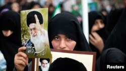 FILE - A woman holds pictures of Iran's Supreme Leader Ayatollah Ali Khamenei (top) and late Leader Ayatollah Ruhollah Khomeini during a rally to mark the 32nd anniversary of the Islamic Revolution in Qom, February 11, 2011. REUTERS/Morteza Nikoubazl