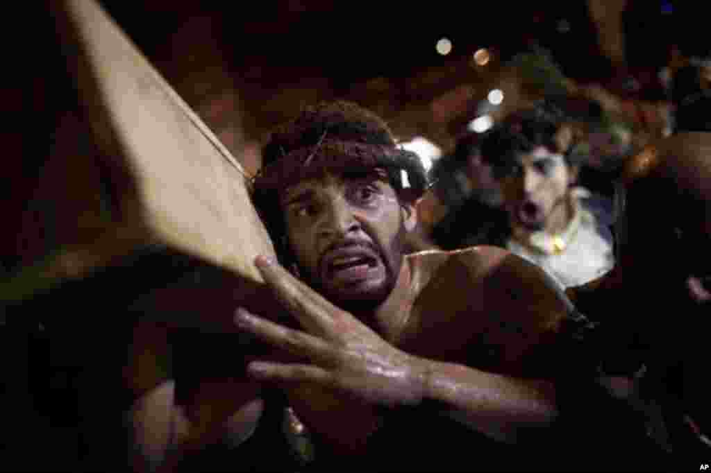 A man participates in a reenactment of the Passion of Jesus Christ on Good Friday during Holy Week celebrations at Rocinha slum in Rio de Janeiro, Brazil, Friday April 6, 2012. Holy Week commemorates the last week of the life of Jesus, culminating in his