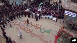 "In this image from amateur video made available by the Shaam News Network and shot on Friday, December 30, 2011, protesters gather in Homs, Syria. The writing on the ground, in Arabic, reads: ""We are those who seek freedom and peace. We are not thieves or"