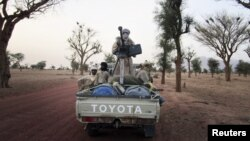 Militiaman from the Ansar Dine Islamic group ride on an armed vehicle between Gao and Kidal, northeastern Mali, June 12, 2012.