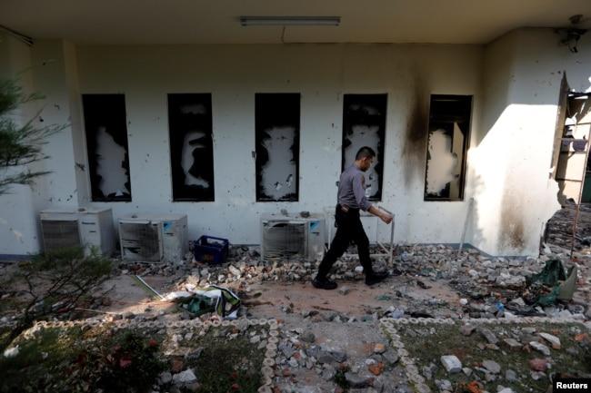 Seorang polisi berjalan melintas jendela yang rusak dalam kerusuhan yang terjadi setelah pengumuman hasil resmi pilpres di Badan Pengawas Pemilu (Bawaslu) di Jakarta, 23 Mei 2019.