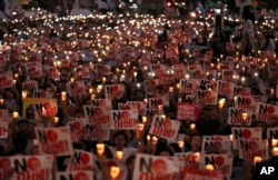 Protesters hold candles and signs during a rally denouncing Japanese Prime Minister Shinzo Abe and also demanding the South Korean government to abolish the General Security of Military Information Agreement, or GSOMIA