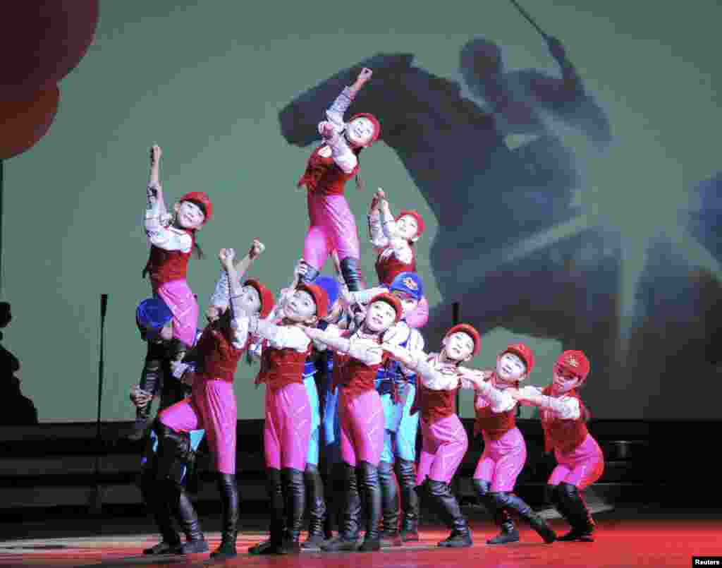 "In a photo released by North Korea's Korean Central News Agency, schoolchildren perform ""We Are the Happiest in the World"" at the Central Youth Hall for New Year's Eve festivities in Pyongyang."