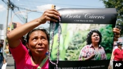 FILE - A woman holds up a poster with a photo of slain environmental leader Berta Caceres, during a protest march in Tegucigalpa, Honduras.