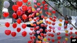 A vendor arranges heart-shaped balloons along the roadside to attract customers ahead of Valentine's Day, in Lahore, Pakistan, Feb. 13, 2016.
