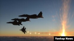 지난해 12월 일출을 배경으로 F-15K 전투기가 플레어를 발사하며 기동하고 있다. '플레어'는 열을 감지하여 추적해 오는 적 미사일을 교란시키기 위한 회피 무장을 말한다. (자료사진)