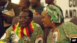 President Robert left listens to his wife Grace at a Zanu PF Conference. (AP File Photo/Tsvangirayi Mukwazhi)