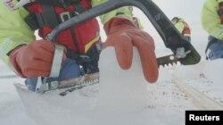 Seorang ilmuwan dari Proyek Northwest Passage pimpinan AS memotong inti es yang dibor dari Arktika Kanada dalam ekspedisi 18 hari pada Juli dan Agustus 2019. (Foto: Northwest Passage Project via Reuters)