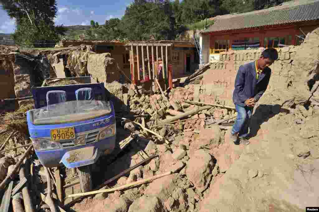 Seorang pria melewati rumahnya yang ambruk setelah gempa 6,6 Skala Richter di Minxian, provinsi Gansu.