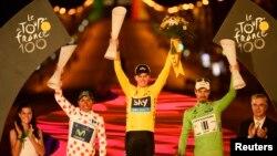 Pebalap sepeda Inggris dari Team Sky, Christopher Froome (tengah) saat menerima trophy sebagai juara Tour de France ke-100 tahun ini Minggu di Paris (21/7). (Reuters/Bernard Papon)