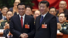 China's President Xi Jinping shakes hands with China's newly elected Premier Li Keqiang (L) as other delegates clap during the fifth plenary meeting of the first session of the 12th National People's Congress (NPC) in Beijing, March 15, 2013.