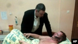 Pemimpin oposisi Ukraina Vitali Klitschko, berbicara dengan Dmytro Bulatov di rumah sakit di Kiev, Ukraina, 31/1/2014.