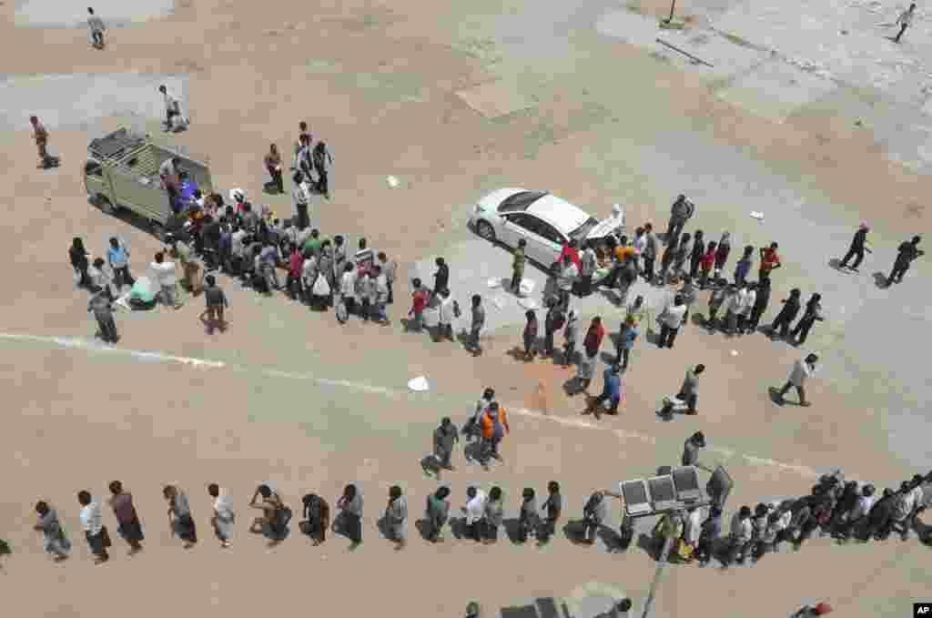 گروهی از مردم فقیردر حیدرآباد، هند در صف دریافت مواد غذایی رایگان.