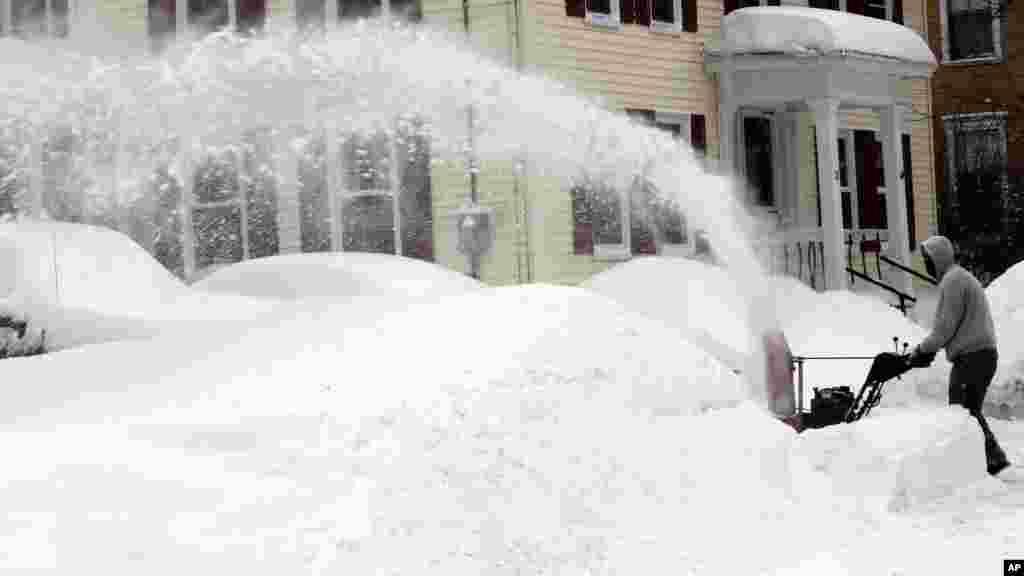 Un homme enlève la neige à Concord, NH, diamnche 16 février 2015.