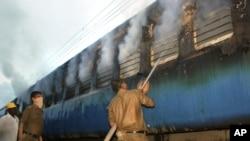 Nhân viên cứu hỏa Ấn Ðộ phun nước vào toa xe lửa bị hỏa hoạn ở thị trấn Nellore, ngày 30/7/2012