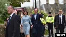 Perdana Menteri Inggris David Cameron tiba dengan istrinya Samantha untuk memberikan suara di Spelsbury, Inggris tengah (7/5). (Reuters/Toby Melville)