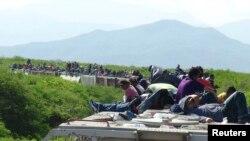"""Migrantes centroamericanos viajan a bordo de """"La Bestia""""."""