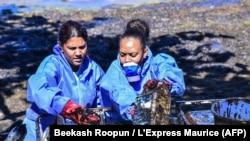 Deux bénévoles recueillent les fuites de pétrole du vraquier MV Wakashio qui s'était échoué sur la plage de Mahébourg, au sud-est de l'île Maurice, le 12 août 2020. (Photo: Beekash Roopun / L'Express Maurice / AFP)