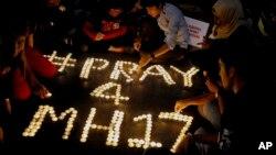 Warga menyusun lilin untuk menghormati para korban jatuhnya pesawat Malaysia Airlines penerbangan MH17, di sebuah pusat perbelanjaan di Petaling Jaya, dekat Kuala Lumpur, Malaysia (18/7). (AP/Joshua Paul)
