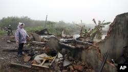 段文旺的妻子2012年2月4日站在他们被摧毁的房屋的瓦砾旁
