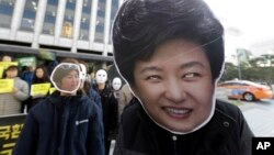 South Korean protesters wearing masks of South Korean President Park Geun-hye, right, and Choi Soon-sil, who is at the center of a political scandal, stage a rally calling for Park to step down in downtown Seoul, South Korea, Nov. 2, 2016.
