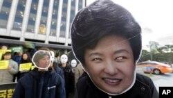 南韓民眾在首爾街頭戴上總統朴槿惠的面具抗議,要求總統下台。