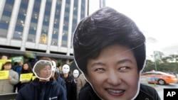 Manifestan nan Kore di Sid mete mask ki sanble ak Prezidan Park jeen-hye, pandan yon rasanbleman nan vil Seoul, Kore di sid, 2 nov, 2016.