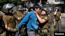 A demonstrator is detained during a protest against Chile's government in Concepcion, Chile