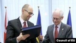 Thủ tướng lâm thời Ukraina Arsenyi Yatsenyuk (trái) và Chủ tịch Hội đồng châu Âu Herman Van Rompuy trao đổi tài liệu tại lễ ký hiệp ước ở Brussels, 21/3/2014.