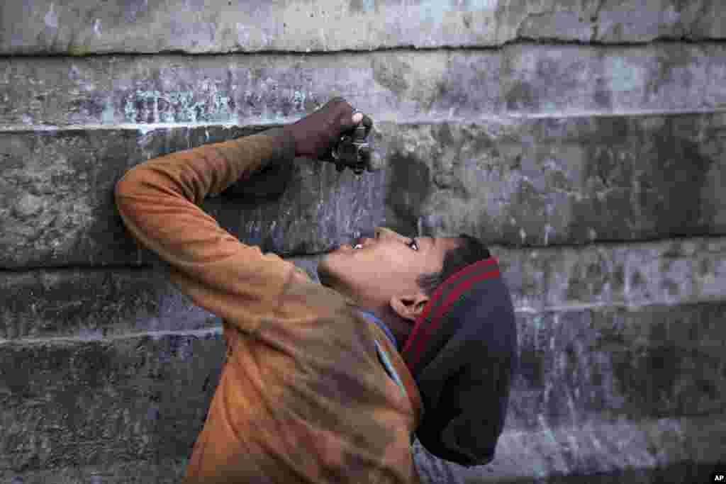 一名印度拾荒少年在印度查谟郊区的一个汽车推场地的一个水龙头喝水。