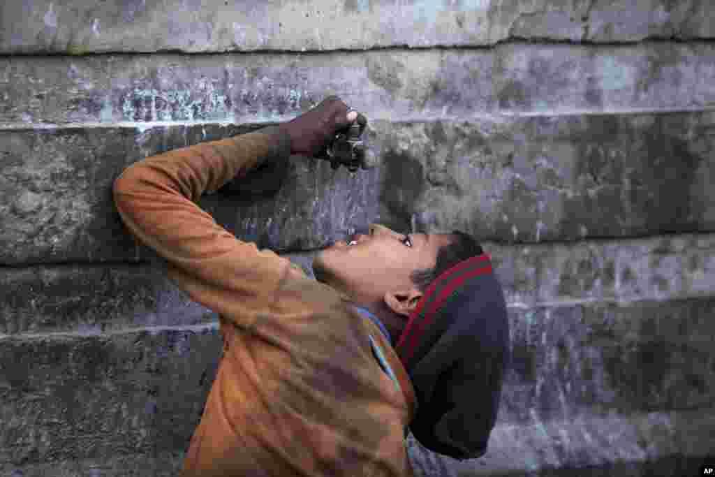 An Indian ragpicker boy drinks water from a tap at an automobile yard on the outskirts of Jammu, India.
