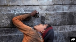 FILE - An Indian ragpicker boy drinks water from a tap at an automobile yard on the outskirts of Jammu, India.