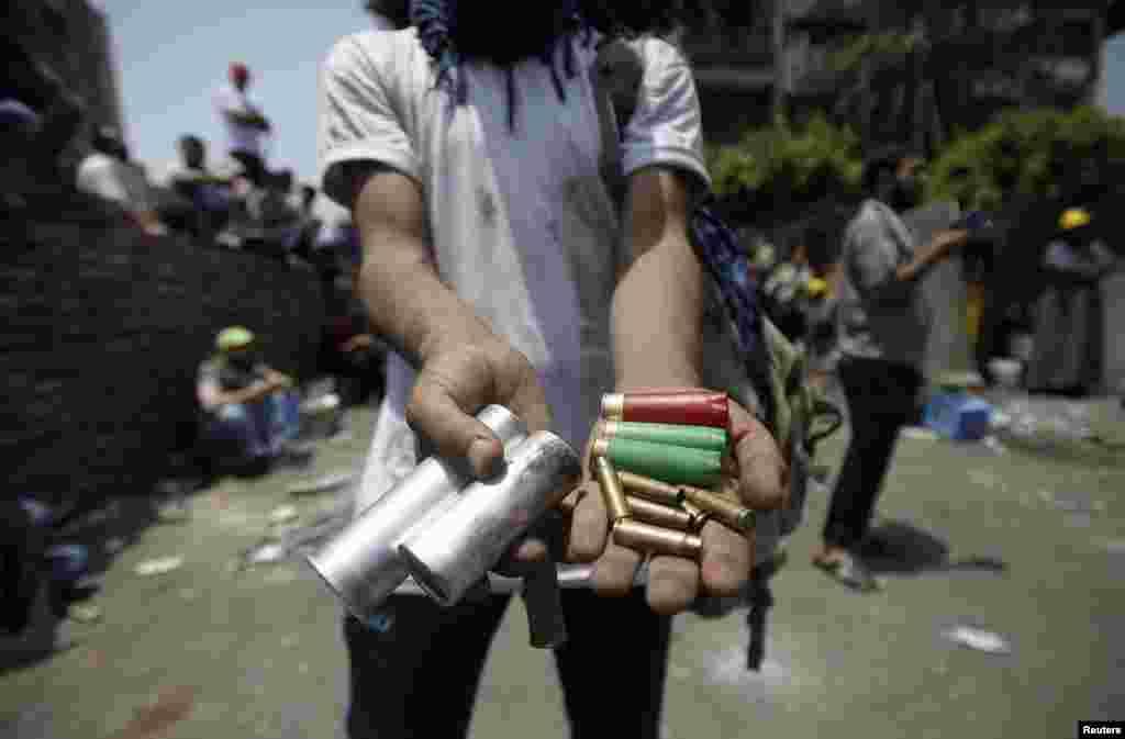 8일 이집트 카이로 외곽 지역에서 군부와 시위대의 충돌이 있은 후, 무슬림 형제단 일원이 총격전에 사용된 총알을 보이고 있다.