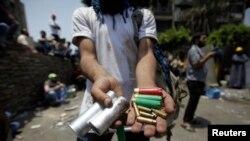 Seoranh pendukung Presiden terguling Mohamed Mursi menunjukkan amunisi yang digunakan pihak militer dalam bentrokan dengan demonstran di Kairo Senin pagi (8/7).