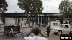 Un homme prend une photo de l'édifice du Parlement brûlé à Ouagadougou, capitale du Burkina Faso 31 octobre 2014.
