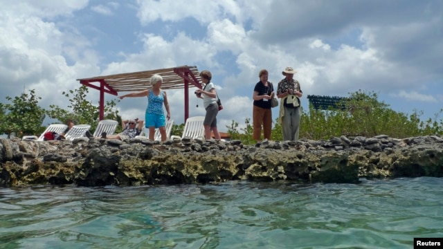 "U.S. ""people-to-people"" tourists stand beside a natural sea pool in the Zapata Swamp in southern Cuba, April 7, 2012."