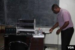 Physicist Ketevi Assamagan demonstrates how a cloud chamber works. (A. Phillips/VOA)