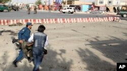 Afghan security personnel carry an injured man after an attack near the Kabul Airport, in Kabul, Afghanistan, July 22, 2018.