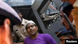 Polisi mengawal salah satu dari empat orang pelaku tindak perkosaan wartawan foto, menuju ruang sidang di pengadilan Mumbai (20/3).
