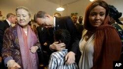 L'ancien secrétaire général des Nations Unies, Ban Ki-moon, au centre, accompagné de sa femme Yoo Soon-taek, embrasse un enfant lors d'une rencontre avec des réfugiés et des demandeurs d'asile dans un centre géré par l'ONG catholique Saint Egidio à Rome samedi, 17 octobre 2015.