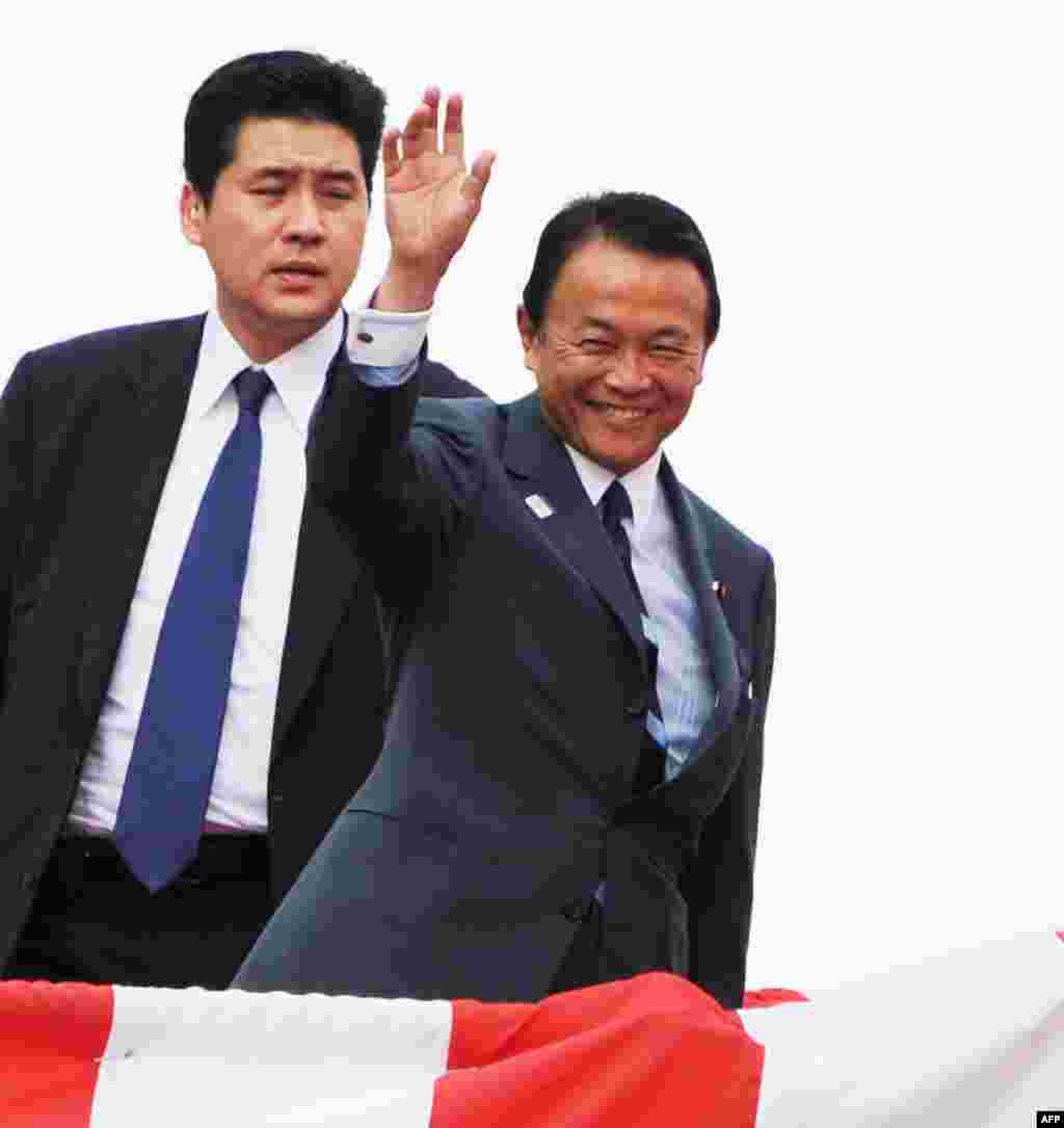 Japanese Finance and Deputy Prime Minister Taro Aso waves to guests while attending the launch ceremony for Japan's newest warship at the port in Yokohama, August 6, 2013.