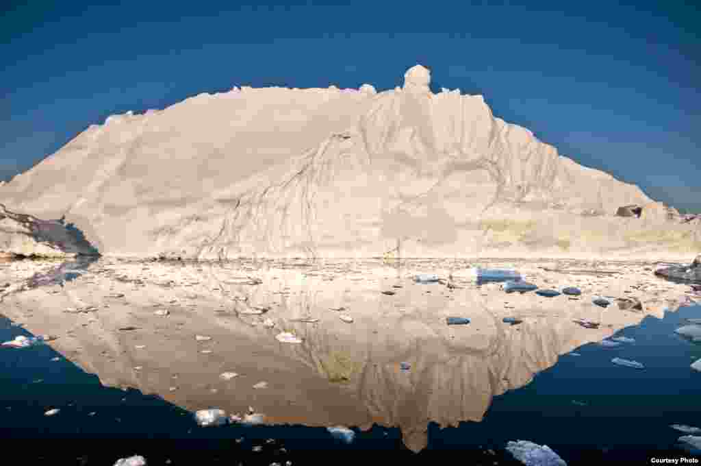 The midnight sun casts a golden glow on an iceberg and its reflection in Disko Bay, Greenland. Much of Greenland's annual mass loss occurs through calving of icebergs such as this. (Photo courtesy Ian Joughin)