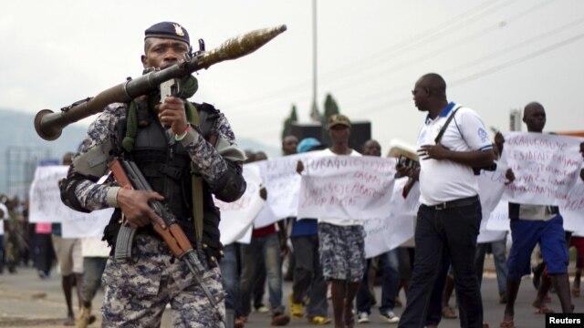 A Burundian soldier walks infront of residents during a demonstration against the Rwandan government in Burundi's capital Bujumbura, Feb. 20, 2016.