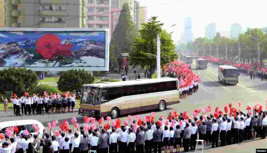 북한이 중장거리 탄도미사일 '화성-12' 개발자들을 평양으로 불러 대대적인 경축 행사를 했다. 개발자들을 태운 버스가 지나가자 북한 주민들이 꽃술을 흔들며 환영하고 있다.
